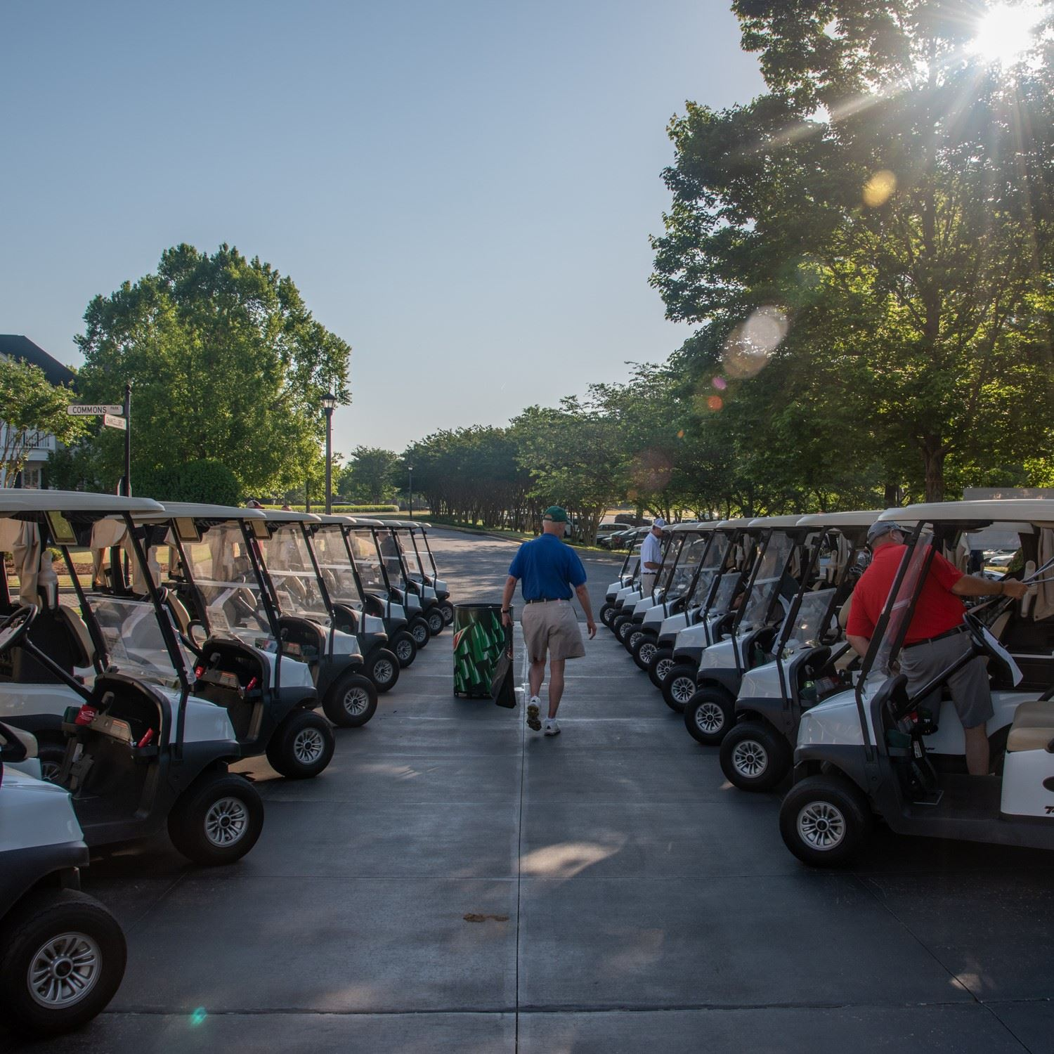 golfer walking through rows of carts